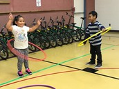 Children enjoying staying active with hula hoops.
