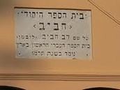 שלט בית הספר משנות החמישים של המאה העשרים.