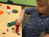 Alex practices cutting playdough worms.