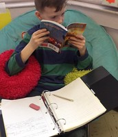 Tyler getting comfy with his reading binder and a good book!