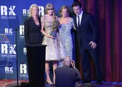 Taylor winning an award with her mom and dad
