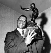 Ernie Davis holding the Heisman trophy