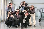 A bunch of paparazzi's taking pictures.
