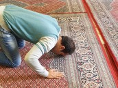 A Muslim prays with  his face on the rug