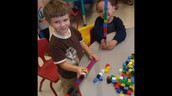 Jacob and Julian compare their tall towers of blocks!