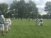 Football players working on tackling.