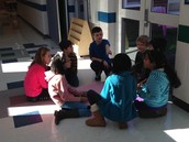 Another group meets and discusses which materials will help them teach about early Virginia!