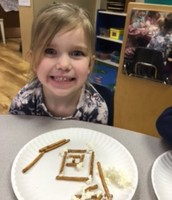 Making log cabins for Presidents Day week with pretzels and cream cheese