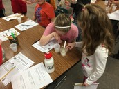 Addie and her Kindergarten buddy observing the chemical reaction between Sta-Flo and Glue
