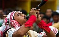 A Bihu dancer blowing a pepa (horn)