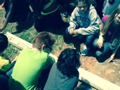 Samuel, Ray, Neveah, and Tiffany observe how erosion happens when water moves rocks and soil.