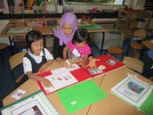 Hasya shows her mummy and sister what she has been busy doing at school
