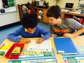Zyir hard at work with help from his fourth grade buddy