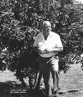 Oskar Schindler standing near a tree planted in his honor in Jerusalem