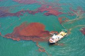 A boat cleans up oil after a spill.
