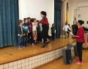 Isla and Axel on stage singing in Spanish at our school Town Hall Meeting