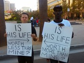 Black & white men with signs about life worth.