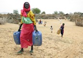 Women are often forced to walk kilometers to gather water for the family.