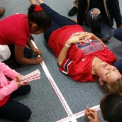 Students measure each other's height in centimeters and record in their math journals.