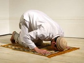 A Muslim praying on his rug in the direction of east(Mecca).