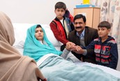 Malala and her family supporting her in the hospital after the gunshot