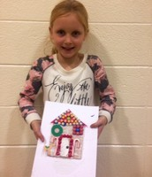 Sam is showing off her yummy Gingerbread house