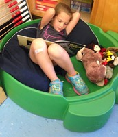 Grace reading with some stuffed animal friends.