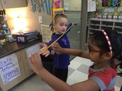 Harshini and Ashlee working together to figure out each other's arm span.
