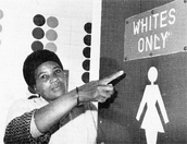 Black woman pointing to whites only sign.