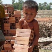 A little kid carrying bricks