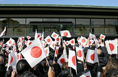 People holding up Japanese Flags