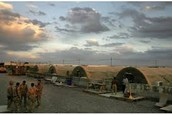 Soldiers stand outside their tents in Afghanistan