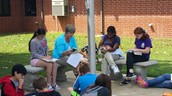 Ms. Tedder reading at the flag pole with students.