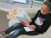 Authentic reading-first grader reading like we do; in a comfortable chair