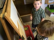 Wyatt and Oona working together at the easel
