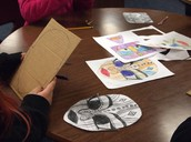 The next step is in the library with the designs being constructed from cardboard.