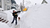 Man shovels driveway as dog looks on.