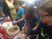 Kanyonrae, Sydney, and Thomas are measuring and mixing the ingredients to make concrete!