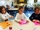 Willa, Caroline and Eve rolling dice and recording the number on their tens frames