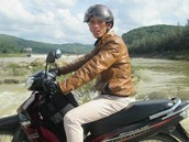 Khoa, on his motorcyle ready to cross a river to teach a church.