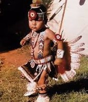 This is a native american child dressed in traditional clothing.