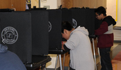 7trh grade students voting in an actual voting booth.