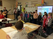 Mrs. Spillane getting her class ready to carol at Bridges