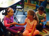Abigail and Savanna greeting one another in morning meeting.