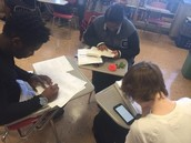Students using phones to research and complete assignments