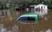 A Home And Car Stuck In Deep Flood Water