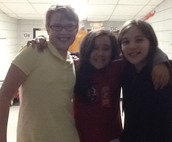 Three friends Lila, Samantha, and Joselienne  are standing close to two games on fun night. Right now the games are gone.