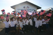 Filipino school children waving US and Philippines flags