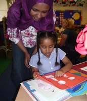 Noor explains her maths work to her mummy