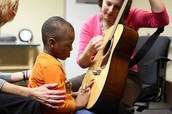 A music therapist visiting with a boy.
